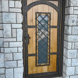 A wrought iron entrance door with wood