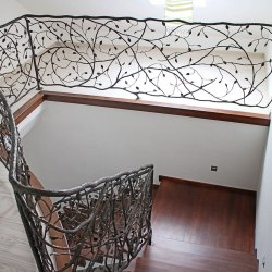A curved hand wrought iron railing
